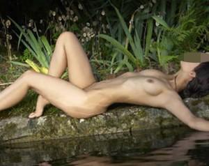 Nacked woman lying near water